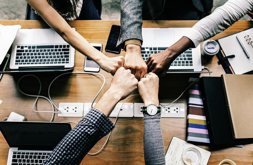 mãos unidas de várias pessoas em uma mesa de trabalho