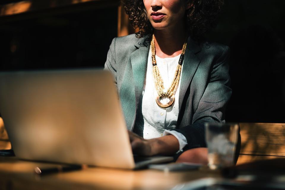 mulher na frente de um laptop digitando